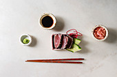 Tuna Sushi sashimi with cucumber in pink ceramic serving plate with chopsticks, bowls of soy sauce, and pickled ginger