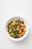 Lentil salad with quinoa, yellow tomatoes, carrots and herbs