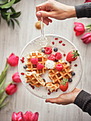 Hands holding dish with delicious waffles and fresh berries on blurred background