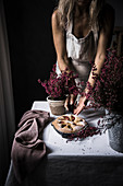 Woman cook in apron cutting plum cake on table with flowers