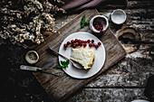 Stück Käsekuchen auf Teller mit roten Johannisbeeren
