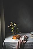 Zitronenkuchen auf rustikalem Tisch mit Blumen