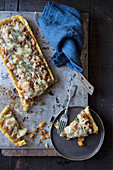 Slice of tart with pumpkin and Emmental cheese on dish with fork placed on tray