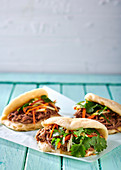 Chinese steamed buns with pulled pork and pickled carrot and apple