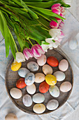 Colourful Easter eggs on a plate with a bunch of tulips