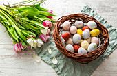 An Easter nest filled with colourful Easter eggs and a bunch of tulips