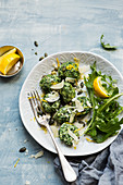 Spinach gnocchi homemade recipe served with mixed leaf salad, parmesan, pumpkin seeds and lemon zest
