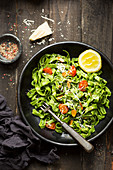 Spinach pasta with cooked cherry tomotoes, parmesan and almonds in a lemon and olive oil dressing