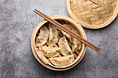 Traditional Chinese dumplings in bamboo steamer with chopsticks
