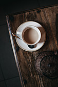 Cup of fresh tea with milk placed on wooden tabletop near metal teapot in dark room