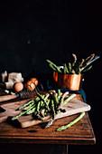 Grüner Spargel, Eier und Käse auf Holztisch