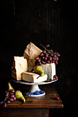 An arrangement of cheese with grapes and pears