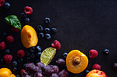 Fresh fruits and berries on dark background (Grapes, blueberries, raspberries with peaches and lime)
