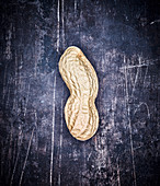 A peanut on a grey metal surface
