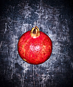 A pomegranate on a grey metal surface