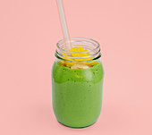 A smoothie made from rocket, mango, banana and milk in a screw-top jar