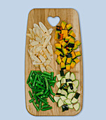 Chopped vegetables (black salsify, pumpkin, courgette, green beans) on a wooden board