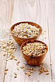 Oat grains and oatmeal in wooden bowls