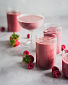 Raspberry and strawberry smoothies in different glasses