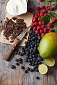 Frische Beeren, Mango, Limettenhälften, Sahne und Schokoraspeln