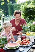 Vater und Tochter beim Picknick mit Erdbeeren und Wassermelone