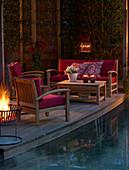 Loungemöbel auf der Terrasse am Pool am Abend bei Kerzenlicht