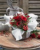 Strauß mit roten Rosen und Hagebutten in Manschette aus Senecio 'Angel Wings'