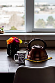 Teacup, tea kettle and a flower vase on a table in front of a window
