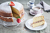 Traditional Victoria sponge with a slice removed and on a plate