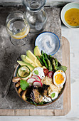 A bowl of avocado, green asparagus, beans, egg, radishes, grilled peach, mint and yogurt