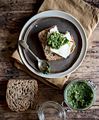 Plate with tasty rye toast with cheese and fresh pesto placed on timber tabletop
