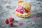Beetroot Ice Cream in a sweet roll on a rustic metal surface decorated with Raspberries