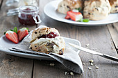 Scones with jam, cream and fresh strawberry on a rustic board