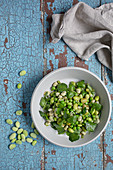 Edamame and Watercress Salad in a White Bowl on a distressed Blue Board