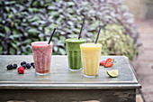 Three smoothies on a garden table