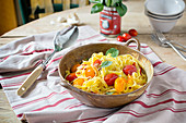Rustic bowl of tomato pasta on a kitchen table covered with striped red linen