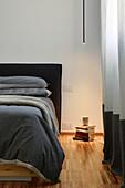 Minimalistische Deckenleuchte beleuchtet Bücherstapel neben dem Bett