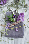 Linen napkin folded into cutlery pouch, hyacinths and violas