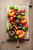 Various types of tomatoes on a wooden cutting board