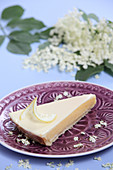 A piece of gin and tonic lemon tart with elderflowers