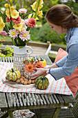 Frau dekoriert Gartentisch mit Dahlien, Gladiolen und Kürbissen