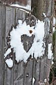 Herz im Schnee auf dem Gartentor