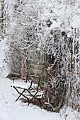Verschneiter Gartenstuhl und Ramblerrose