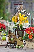 Kleine Osterdeko mit Primeln und Milchstern im Flaschenträger, Weidenkränzchen, Osterhase aus Holz und grüne Ostereier