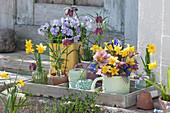Frühlingsdekoration auf Holztablett: Narzissen, Hornveilchen, Schachbrettblumen, Lenzrosen und Netziris