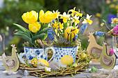 Kleine Oster-Tischdekoration mit Tulpen, Narzissen und Traubenhyazinthen in Tassen, Holz-Hühner und Ostereier als Deko
