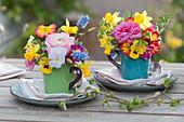 Kleine Frühlings-Tischdekoration mit bunten Sträußchen in Tassen
