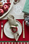 A white ceramic plate with a fork and knife beside it on a Christmas table with a red tablecloth