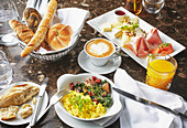 Breakfast with scrambled egg, cheese, sausage, orange juice, coffee and pastries