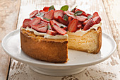 Classic cheesecake with whipped cream and fresh strawberries